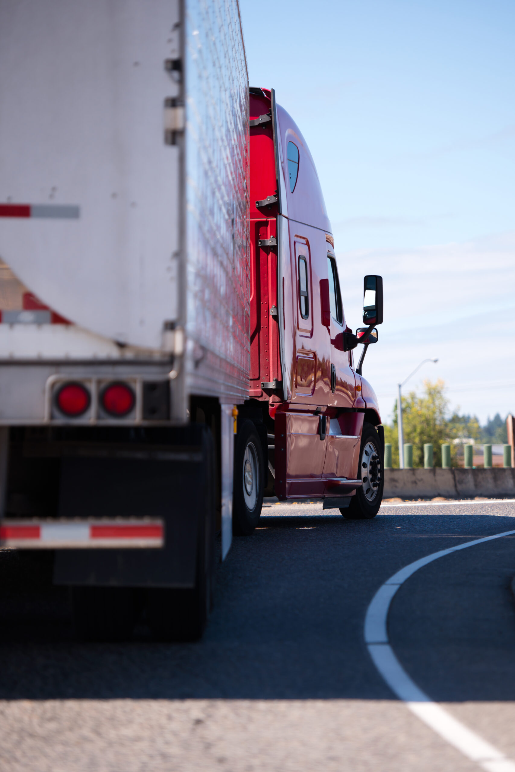 Red modern big rig semi truck with semi trailer turning on the highway entrance